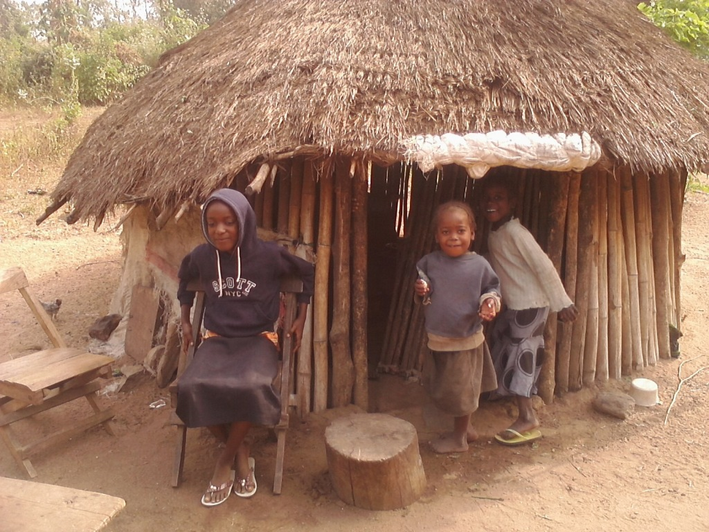 Sitting on the chair is Pastor Seyi Ibitoye's daughter with two of the villagers' children outside their kitchen